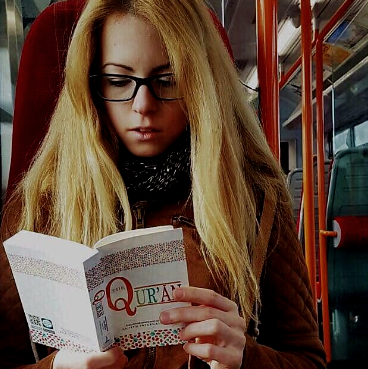 Multiculti Travel Blogger reading the Quran on public transport in London
